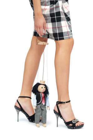 Toy puppet sits near the feet of a young woman. Isolated background