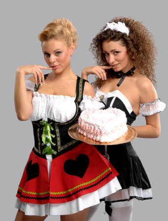 Two pretty waitress with a large cake with cream Stock Photo