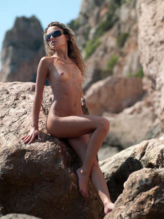 beautiful naked woman sits on a rock. Black Sea coast, Crimea, Ukraine