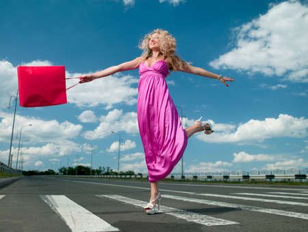 woman in a pink dress with a bag goes over the road photo