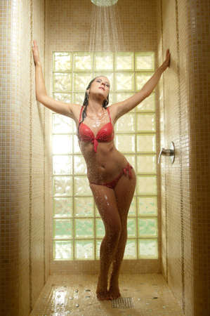 beautiful woman in swimsuit takes shower Stock Photo