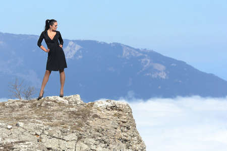 woman in dress standing on a cliff against the sky with clouds Stock Photo