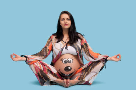 body art: pregnant woman with a pattern on the belly sitting on a blue background