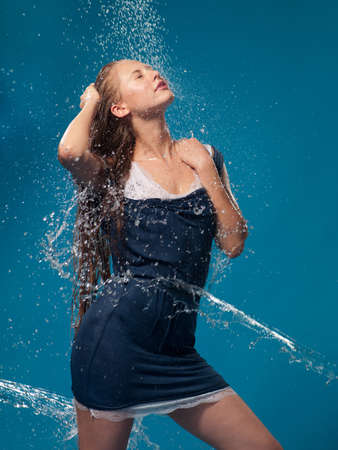 wet lips: woman in a blue dress with running water Stock Photo