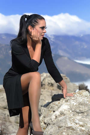 woman in black dress sitting on a rock against the blue sky