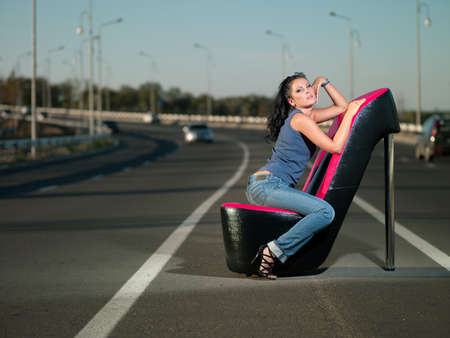 catchy: woman sitting in an armchair on the highway