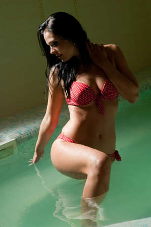 beautiful woman swims in the pool