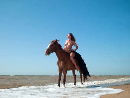 adult only: nude woman on horseback rides along the beach Stock Photo