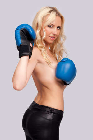 a woman with a bare chest with boxing gloves on a gray background photo