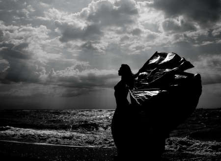 Black and white image of a mermaid on the background of a contrasting sky photo