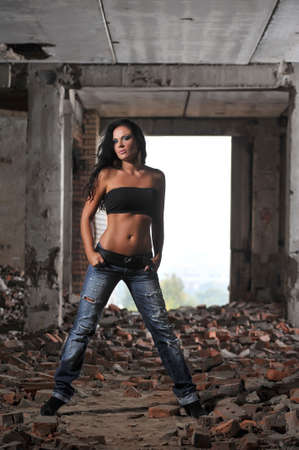 A beautiful brunette in blue jeans on rozvalinah photo