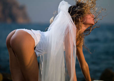 beautiful girl in lingerie in a veil against the sea
