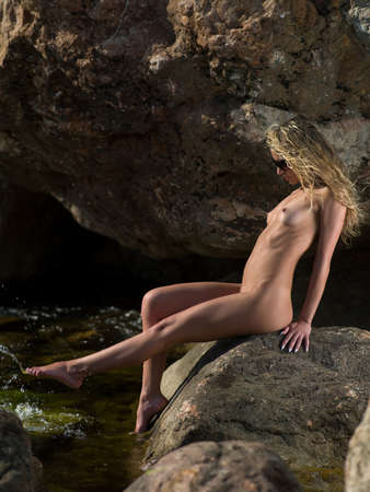 beach babe: bella ragazza seduta su una roccia in riva al mare