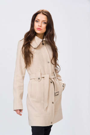 mackintosh: beautiful girl with long hair in a coat on an isolated background