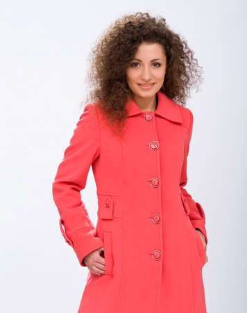 mackintosh: curly girl in a coat on an isolated background Stock Photo
