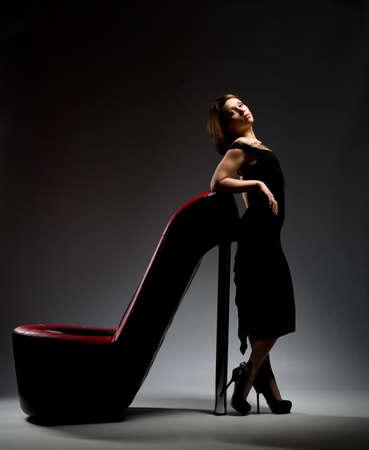 una niña de pie en un zapato sobre un fondo gris