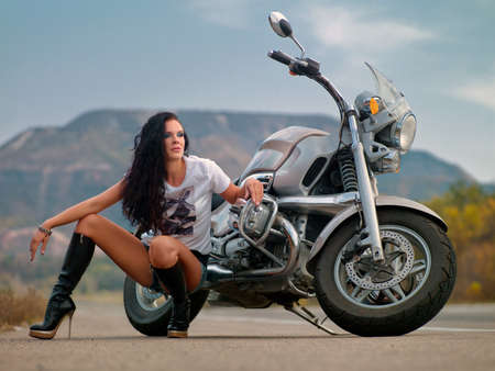 A pretty woman near by motorcycle posing Stock Photo