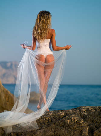 girl in lingerie and veil against the sea