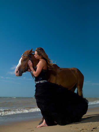 beautiful young girl in dress with a horse on beach photo