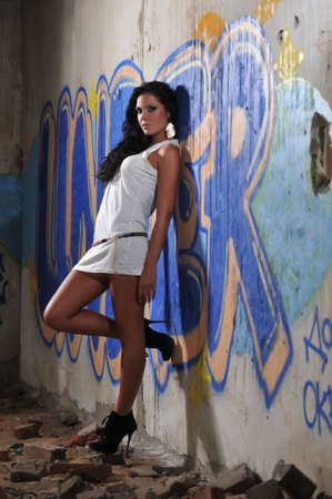 Tanned beautiful girl with bright make-up on the ruins on the background of graffiti Stock Photo