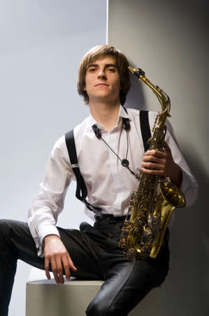 Young man playing the saxophone over white background photo