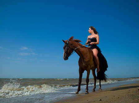 Beautiful girl on a horse near the sea photo