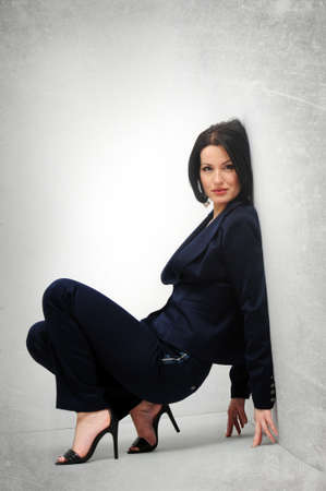 Adult beautiful woman in the pantsuit posing on a white background isolated photo