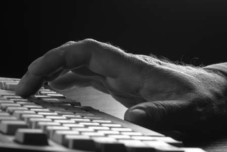 closeup of a mans hand on a keyboard in a low light environment