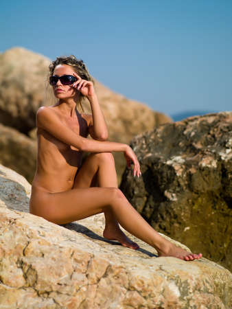 naked girl sitting on rocks with the sky behind her