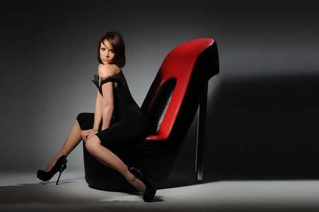 fetysz: Piękna brunetka w stroju wieczorowym siedzi na krześle w kształcie butów Zdjęcie Seryjne