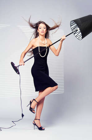 scandalous woman in a black dress with a white floor lamp next  Stock Photo - 13403163