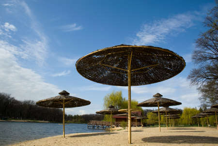 shore of the lake in the sky and trees with beach umbrellas Stock Photo - 13469076