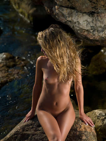 nude woman on the rocks by the sea