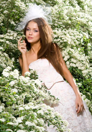 beautiful bride in a hat near the blossoming bush poziuet