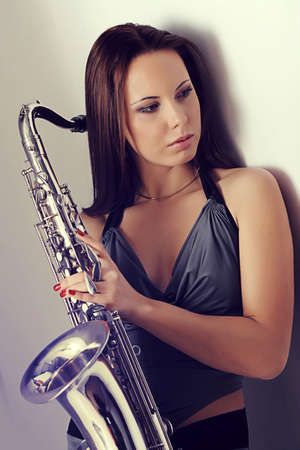 brass: girl standing against a wall and holding a saxophone