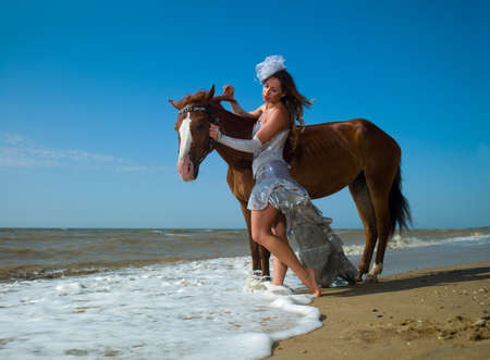 A girl in a white dress beside a horse on the beach photo