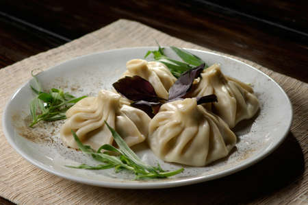meat dumplings served on green plate with vegetables photo
