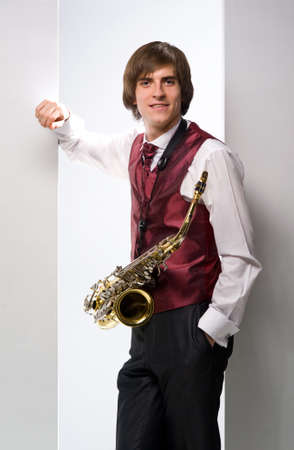 smiling young man in a suit with a saxophone on a white background photo