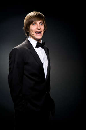 smiling young man in a suit against a black background photo