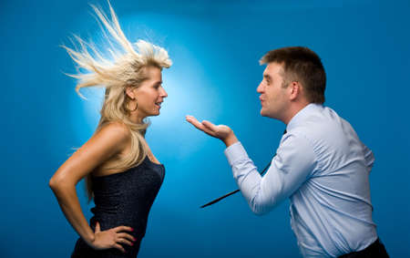 Man blows on the woman from what she had blown her hair