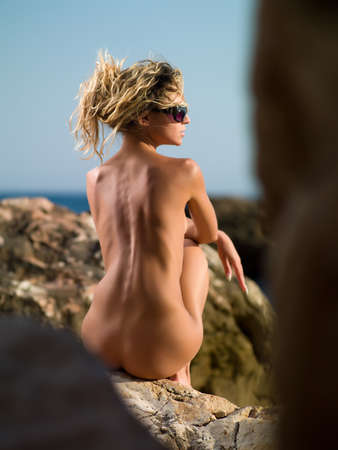 naked girl sitting on the rocks against the sea