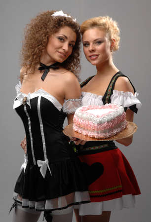 Two girls in dresses are holding a cake photo