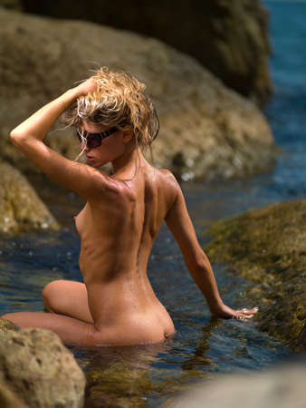 nude girl on the rocks in the water