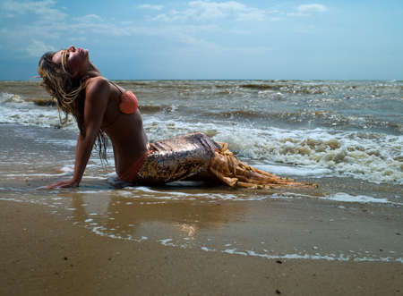 mermaid girl near the coast with a beautiful tail photo