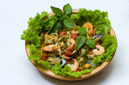 Seafood salad on a plate with green leaves photo