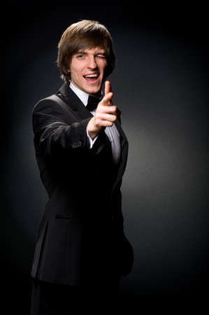 man in black suit smiling solid photo