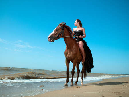 girl in an evening dress on a horse by the sea
