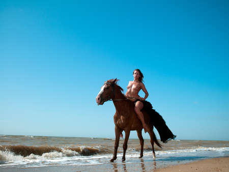 horse laugh: girl in an evening dress on a horse by the sea
