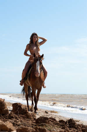 horse laugh: Girl on a horse without a bathing suit is on the beach Stock Photo