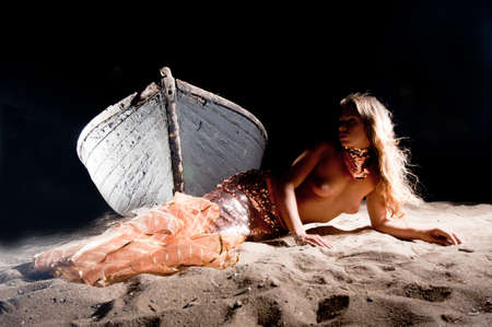 Mermaid girl standing on an old boat on the shore photo